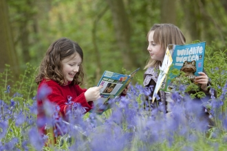 Two kids reading Wildlife Watch magazine among the bluebells in the woods