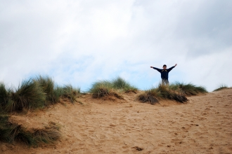 A little boy at Beach School standing triumphantly on top of a sand dune