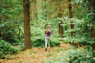 A teenager running through an autumnal pine woodland