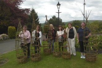 People at a Lancashire Wildlife Trust willow weaving workshop with their finished willow pieces