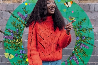 A girl in an orange jumper surrounded by beautiful wildlife illustrations