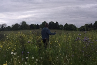 Nature blogger Jennifer Lane walking through a wildflower meadow