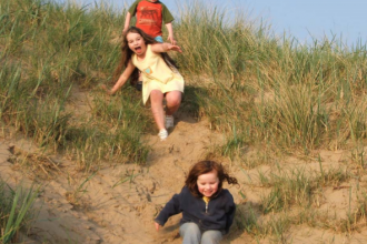 Children sliding down the sand dunes at Beach School in Lancashire