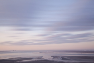 The mudflats of Morecambe Bay on a hazy winter morning at sunrise