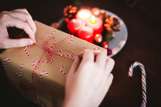 Person wrapping a Christmas present with brown paper and string