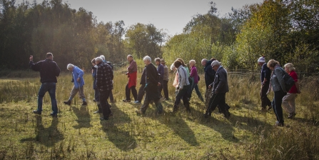 A local group walking at Mere Sands Wood in autumn sunlight