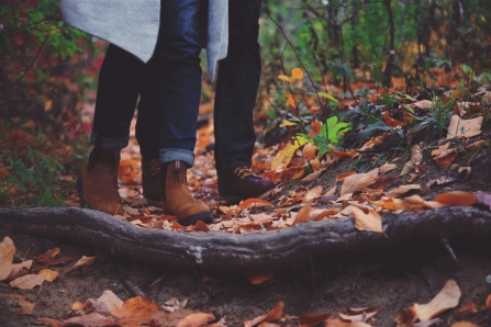 A couple walking through autumn leaves in a woodland