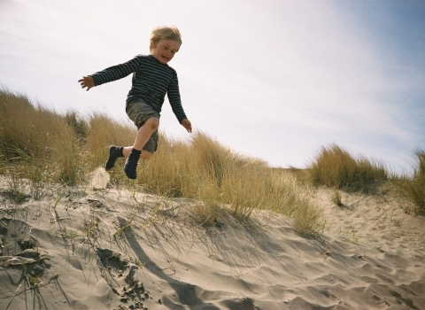 A boy at Beach School leaping down a sand dune on the coast