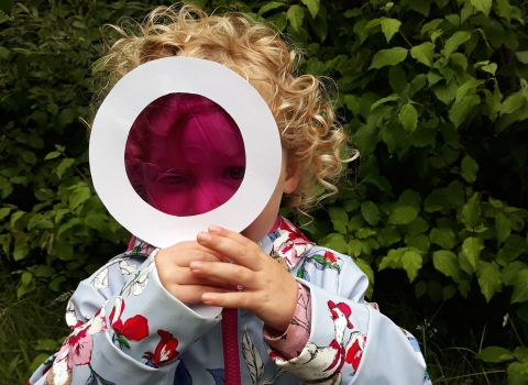 A little girl with a magnifying glass she made at Nature Tots at Heysham Nature Reserve